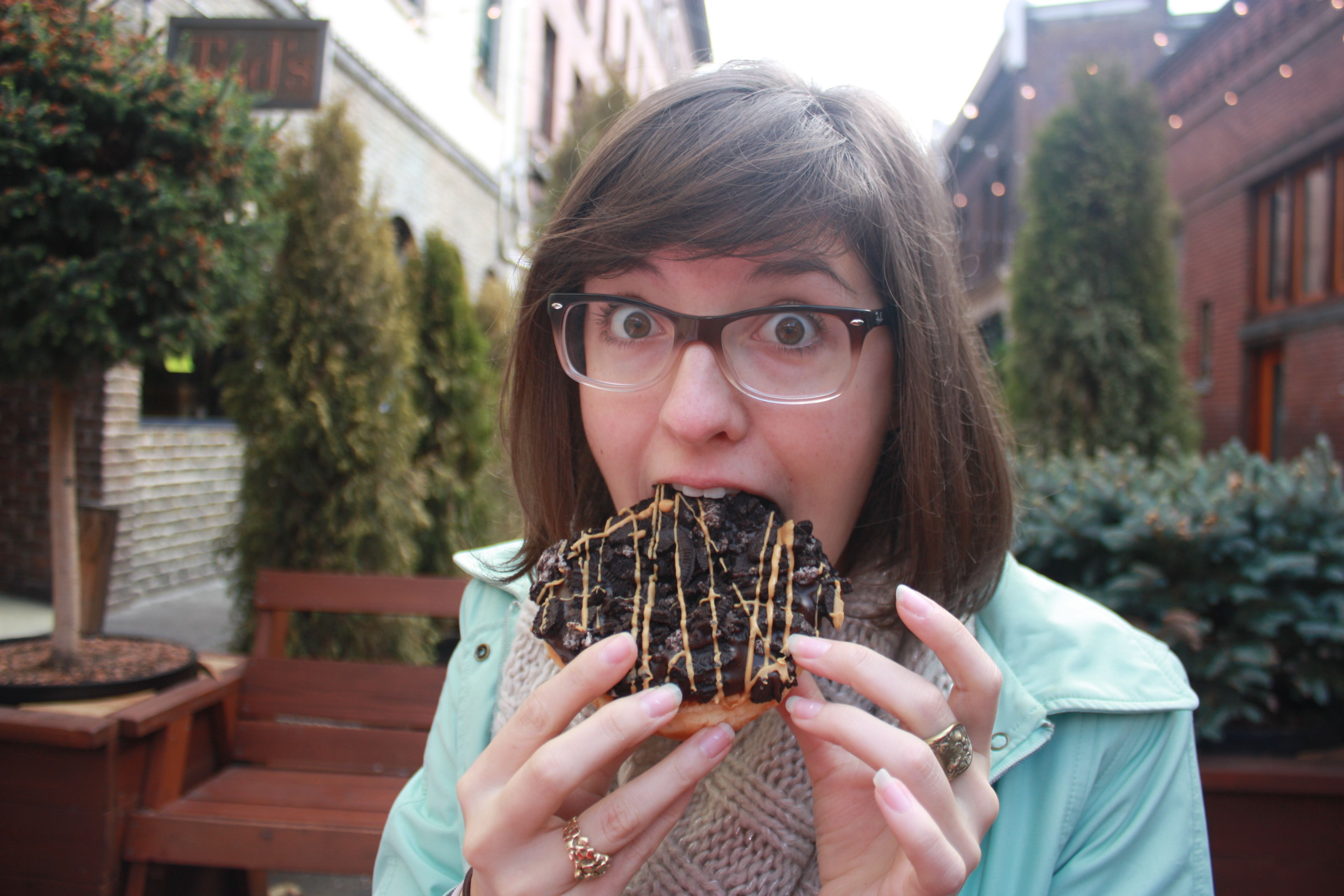 Young Woman Eating Oreo Chocolate Donut Voodoo Donuts Portland Oregon